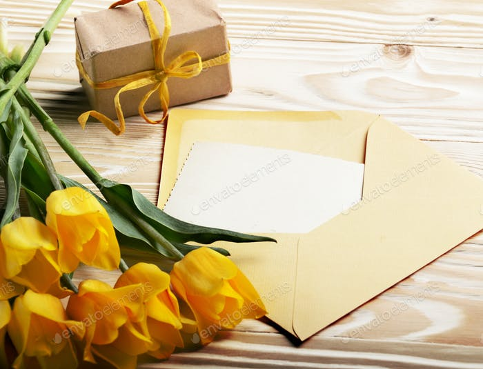 Yellow tulips near blank greeting card gift box and envelope on