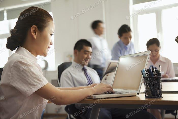 Frau arbeitet an ihrem Laptop im Büro