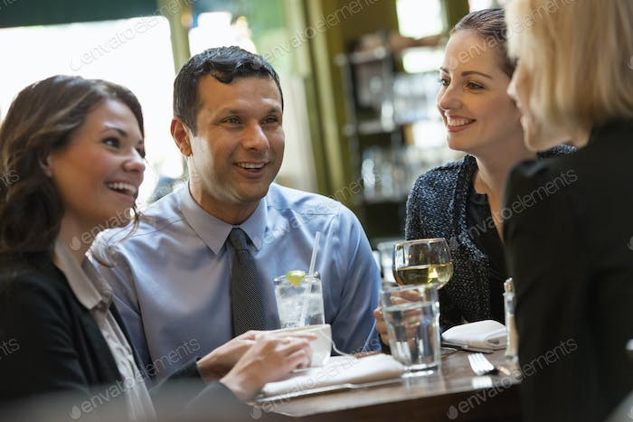 Business people sitting at a table. A meeting or social gathering.