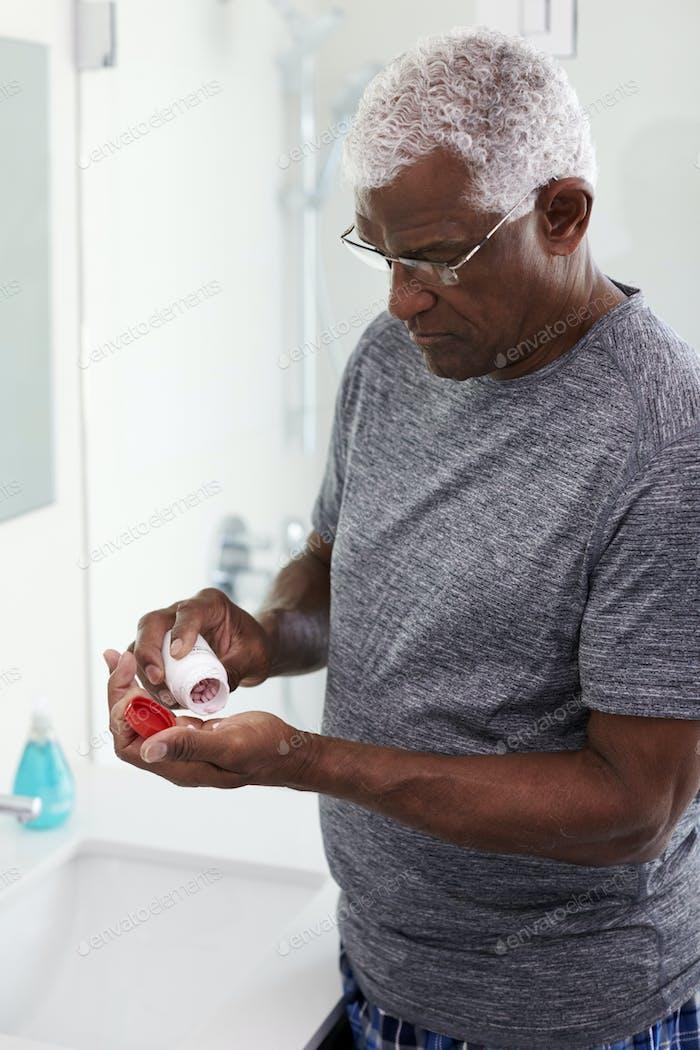 Senior Man In Bathroom Mirror Wearing Pajamas Taking Vitamin Supplement Tablet
