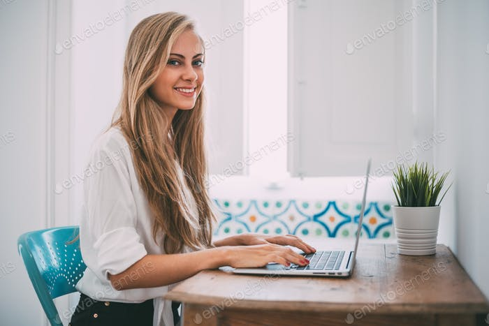 Young beautiful blonde woman on the computer working