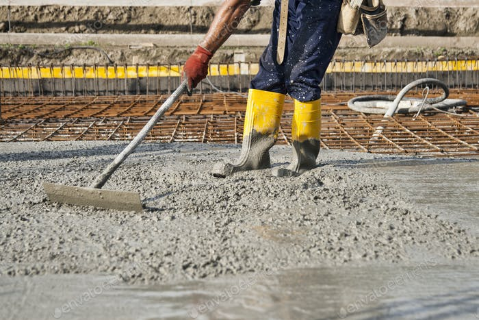 a bricklayer who level the freshly poured concrete to lay the foundations of a building