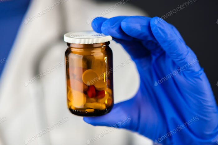 Female doctor holding unlabeled bottle of various pills and medi