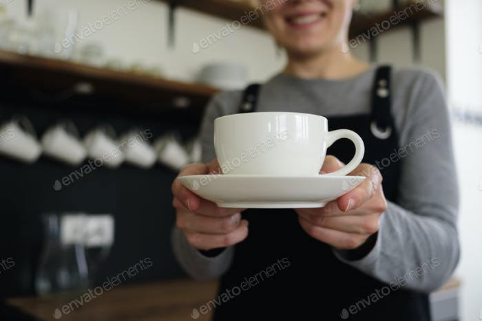 Woman waitress with cup smiling