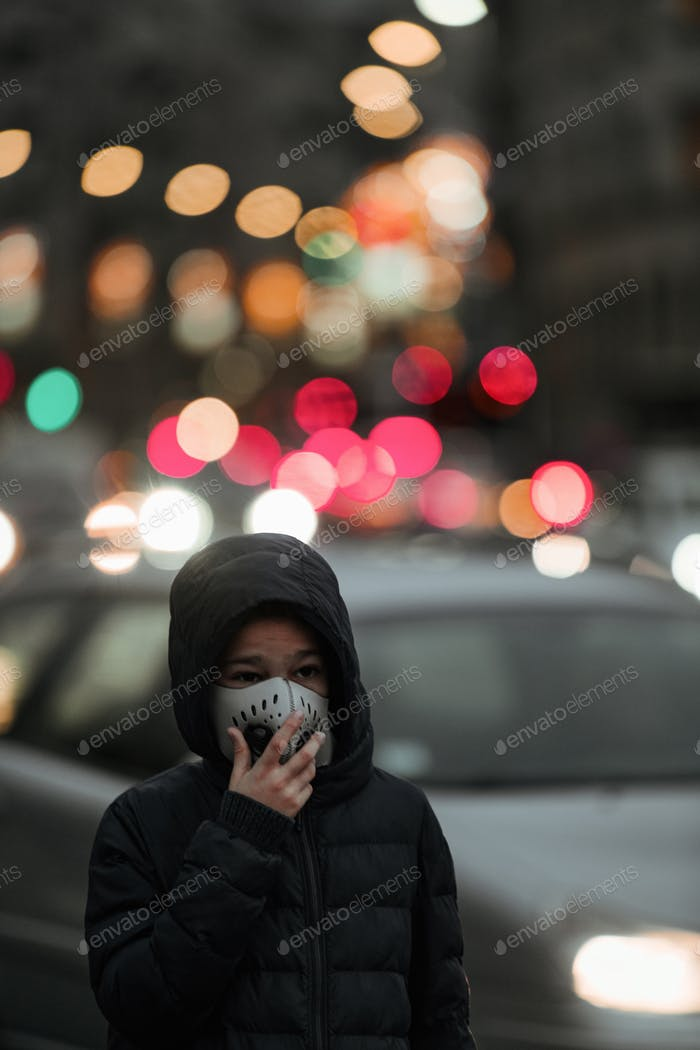 Air Pollution Concept - Young Person with Breathing Mask in the City