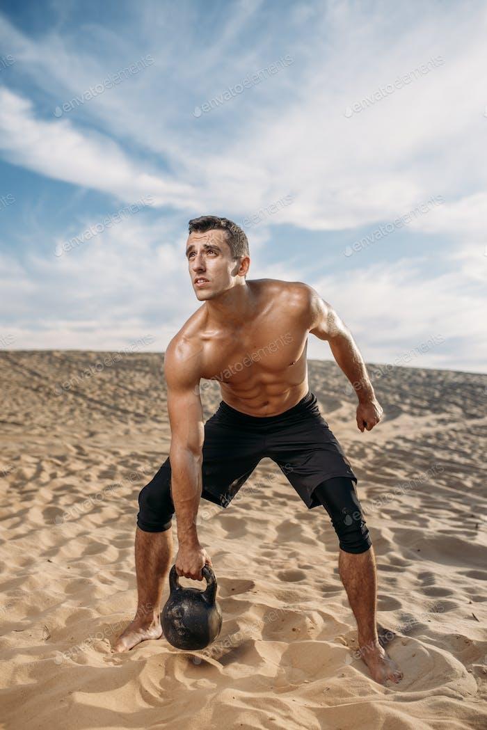 Athlete doing exercise with kettlebell in desert