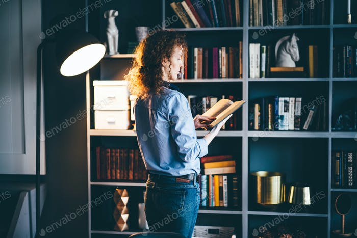 Blond woman reading book and thinking at modern apartment.