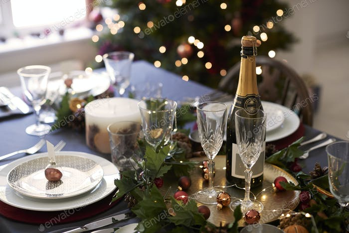 Christmas table setting with glasses and a bottle of champagne
