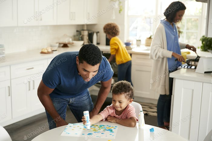 Dad watching his toddler son painting a picture sitting at a table in the kitchen