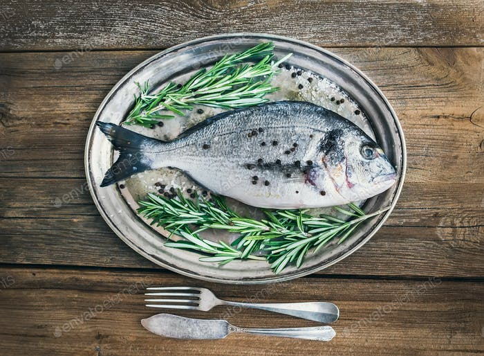 Fresh sea fish (sea bream) on a metal dish with rosemary and spi