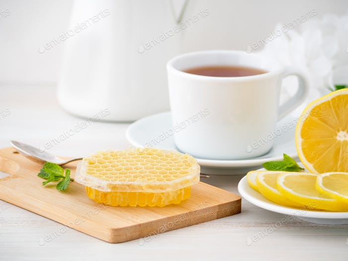 White Cup with tea, lemon slices and honey in honeycomb on white wooden table, side view