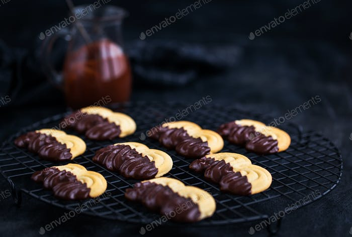Homemade chocolate dipped shortbread cookies on dark background