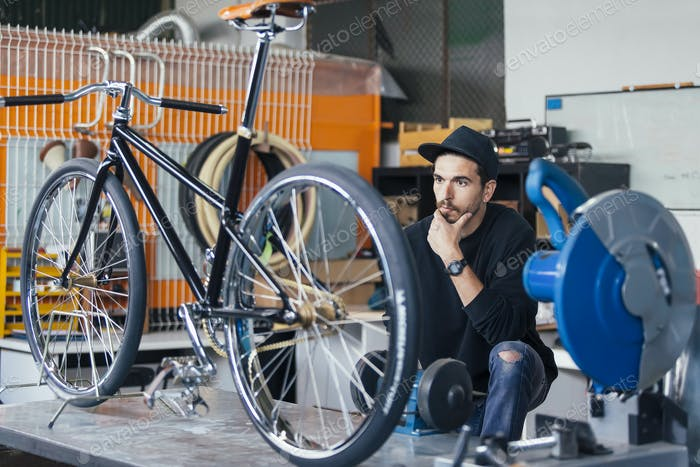 Man in cap looking at his bicycle in workshop