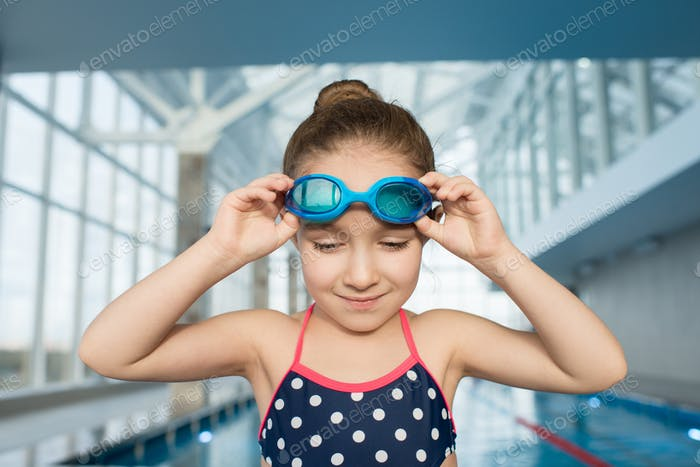 Determined girl adjusting swimming goggles