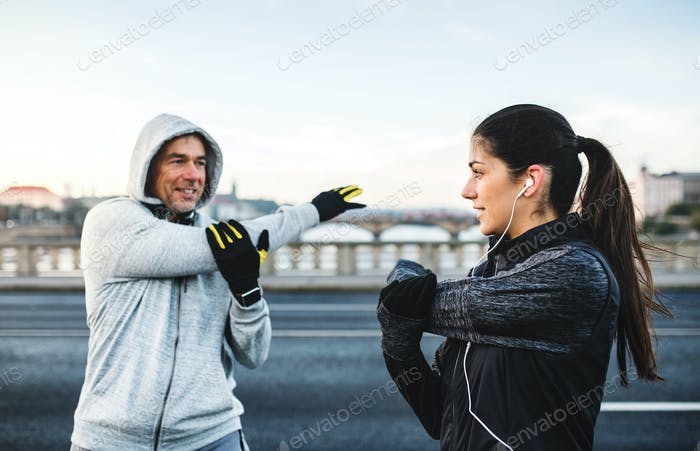A fit couple runers doing stretching outdoors on the bridge in Prague city.