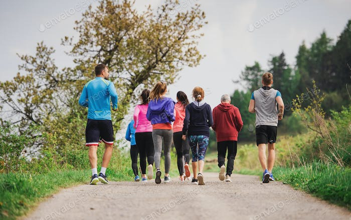 Rear view of group of multi generation people running a race competition in nature