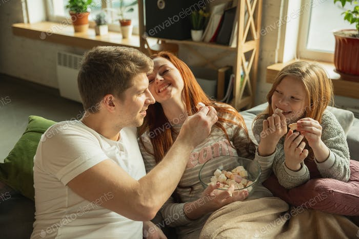 Family spending nice time together at home, looks happy and cheerful, watching TV