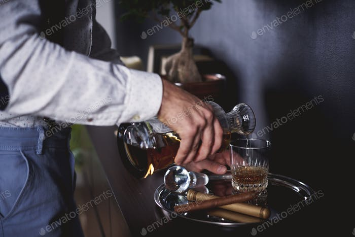 Unerkennbarer Mann gießt ein Glas Whisky