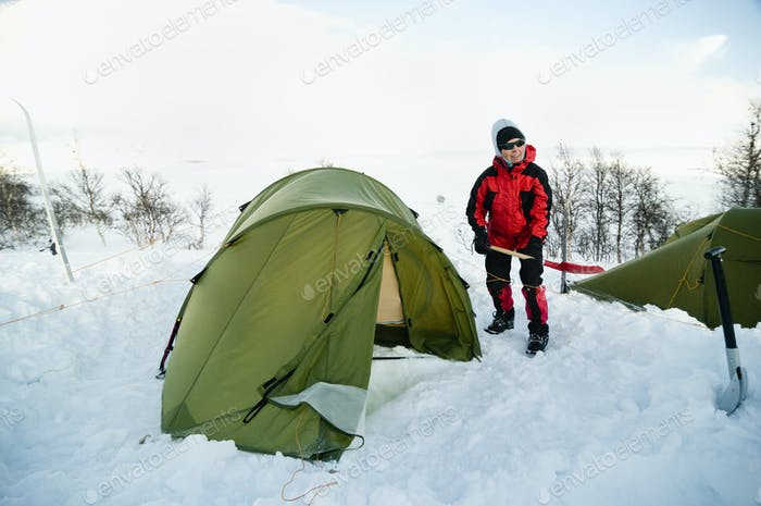 Woman with shovel standing by tent