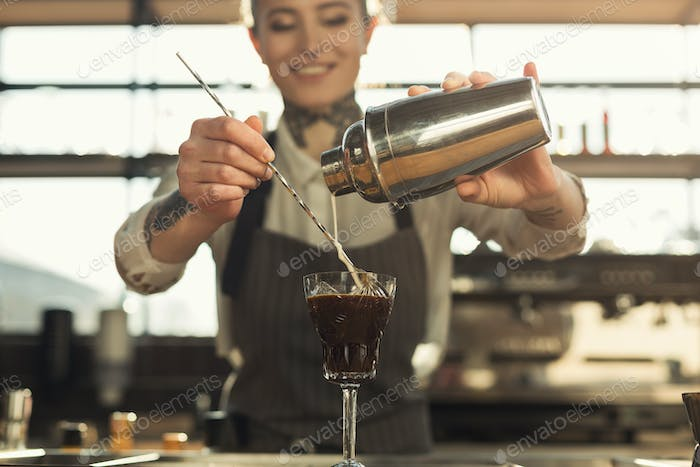 Happy barista making coffee cocktail at cafe counter