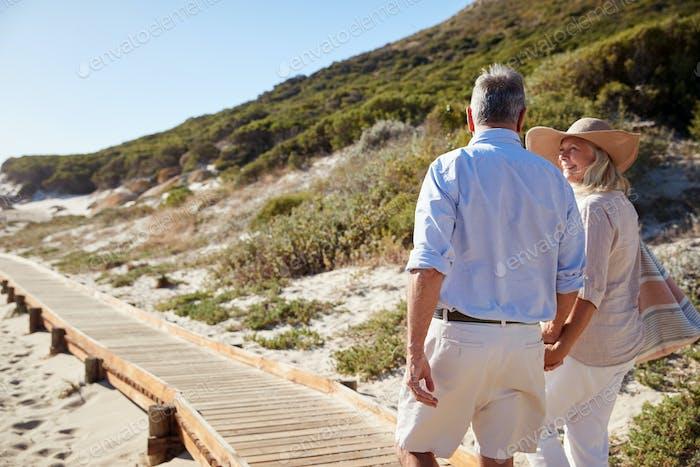 Senior pareja blanca caminando a lo largo de un paseo de De madera en una Playa tomados de la mano, de cerca, vista de atrás