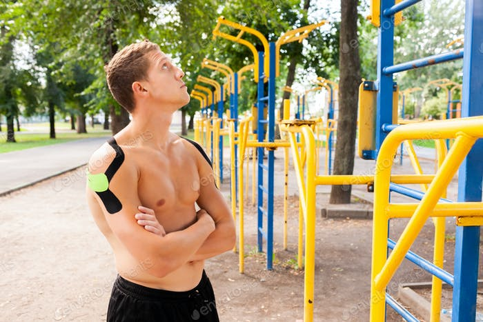 Athlete with kinesiological taping posing near bars outdoors