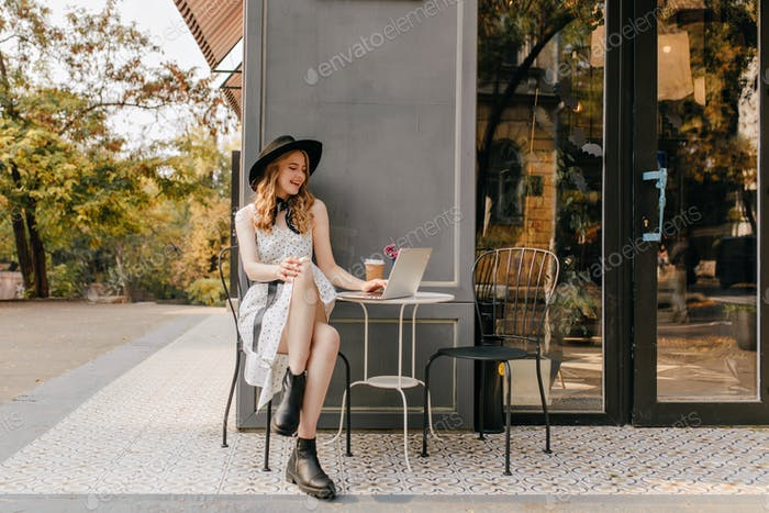 Bright, sensual girl with blond curls and in white summer sundress sits in cafe on the street, chat