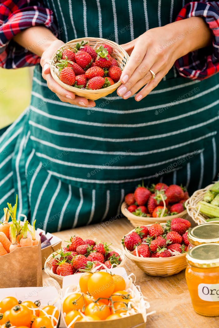 Midsection of woman selling strawberries