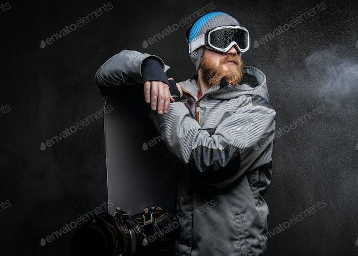 Жестокий рыжий сноубордист, одетый в сноуборд пальто, позируя со сноубордом в студии
