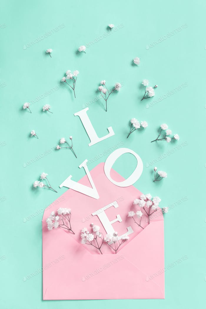 Flowers, pink envelope and word Love on a light green background
