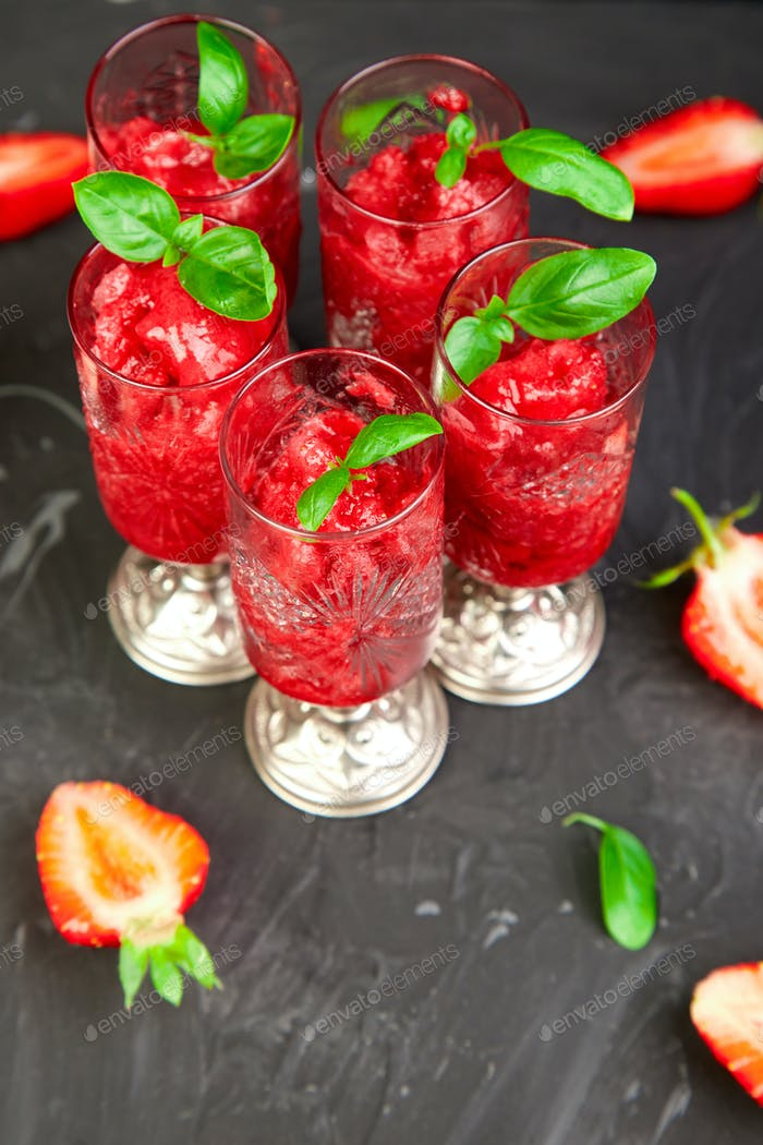 Summer refreshing strawberry sorbet, slush granita drink in serving glasses.