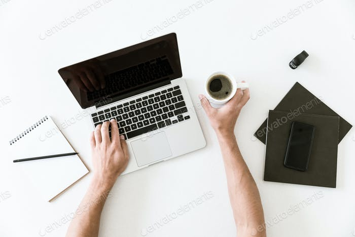 Top view of minimalistic workspace with male hands typing on laptop and holding a cup of coffee