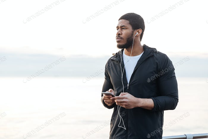 Sportsman standing and listening to music from smartphone outdoors