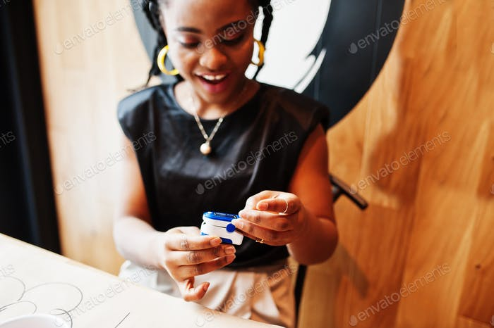 African american women with pulse oximeter on hand measuring oxygen saturation level.