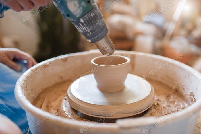Master dries a pot on pottery wheel