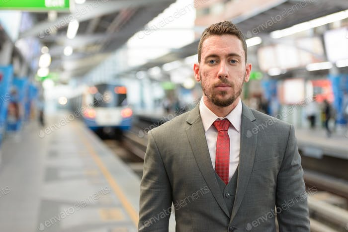Young handsome Caucasian businessman at train station in Bangkok