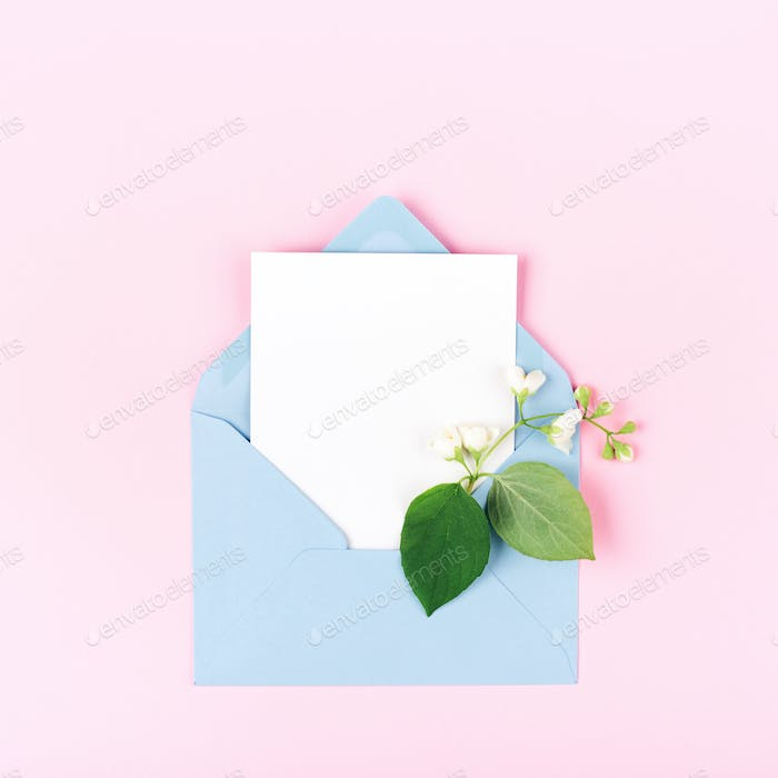 Mockup with Blue Envelope and Jasmine Flower on Pink Background.
