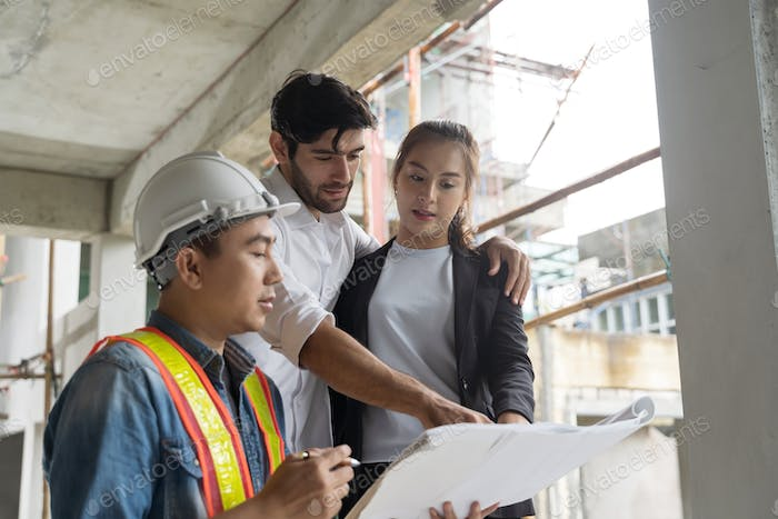Couple checks the work of a contractor building a house for them.