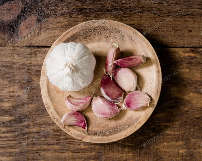 aerial take of whole garlic cloves and heads in rustic wood