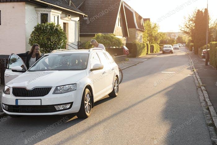 Женщина и мужчина на машине в пригородном районе