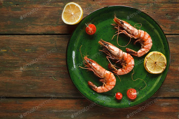 Shrimps with lemon on green plate