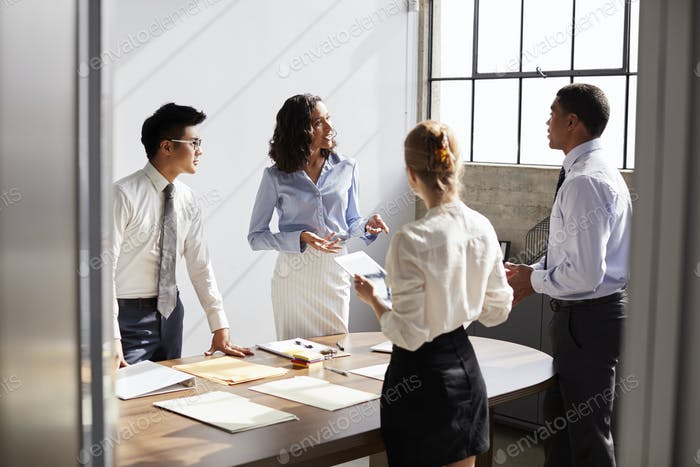 Four business colleagues working together in a small office