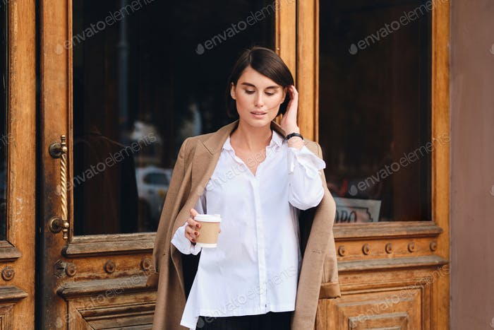 Young beautiful stylish businesswoman with coffee to go dreamily standing outdoor