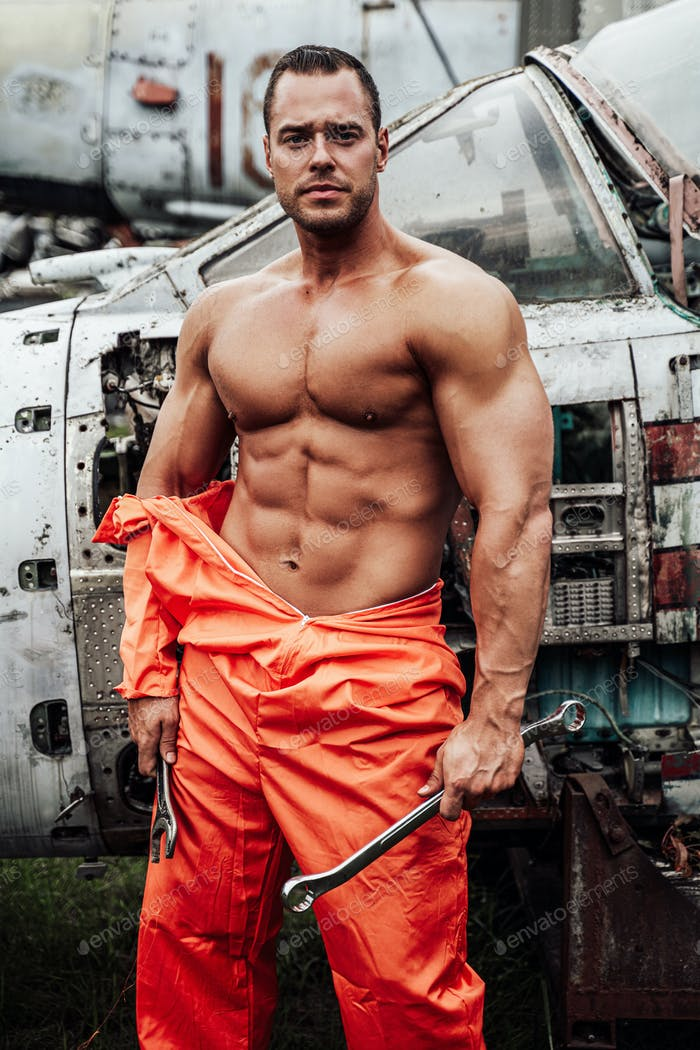 Naked sportsman holds wrenches with airplane behind