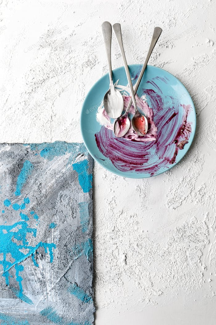 Plate stained after eating on a white textured background with a