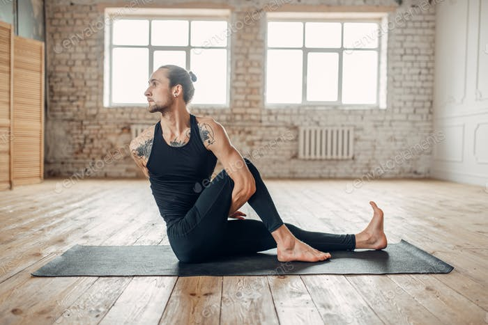 Male yoga in gym, balance exercise on mat