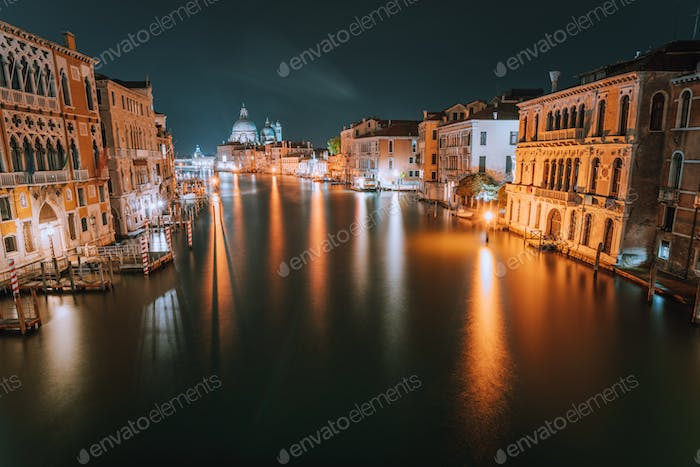 Venice, Italy. Night scene at Grand Canal with reflected light at water surface. Majestic Basilica