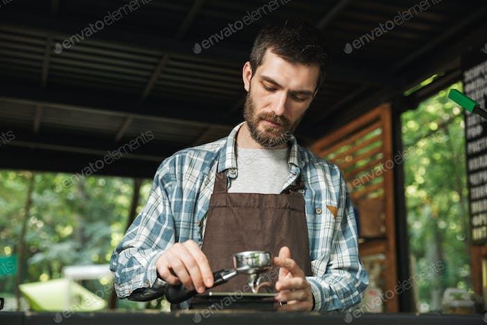 Portrait of handsome barista man making coffee while working in