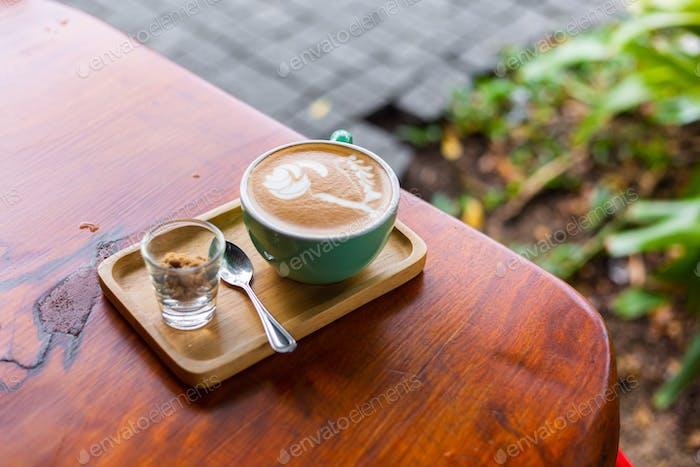 Tasse heißen weißen Kaffee mit braunem Zucker auf Holztisch im Sommercafé im Freien