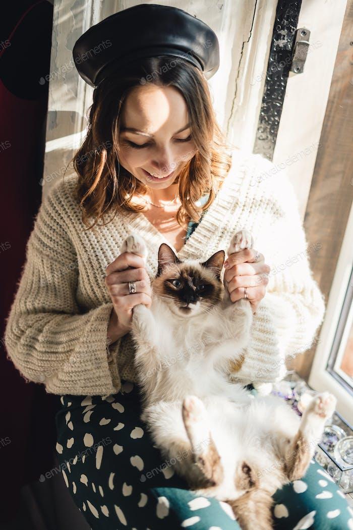 Hübsche Frau hält ihre Katze Pfoten Stretching